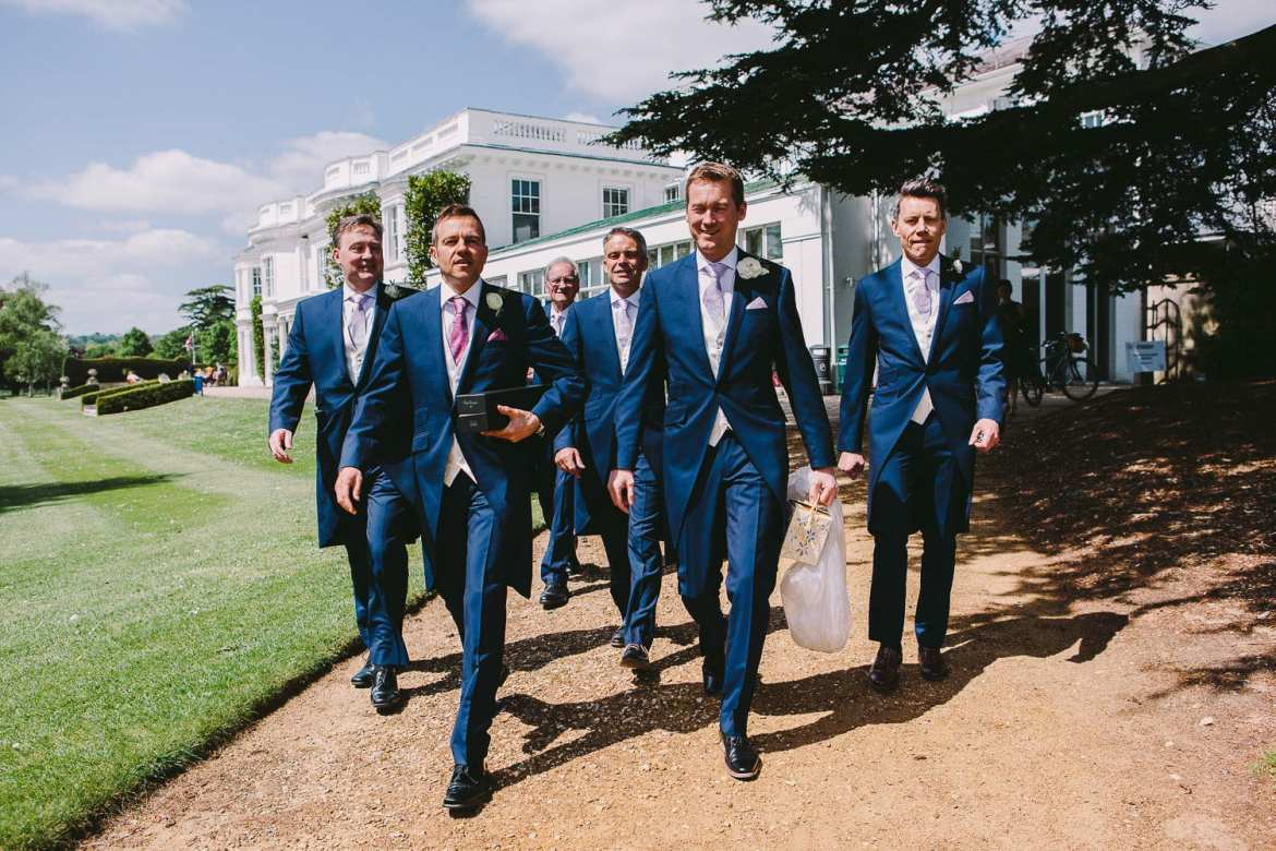The groom and ushers walking to the boat at Greenlands, Henley