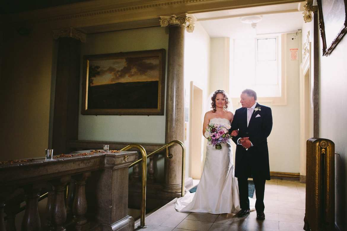 Bride waiting outside the ceremony room with her father
