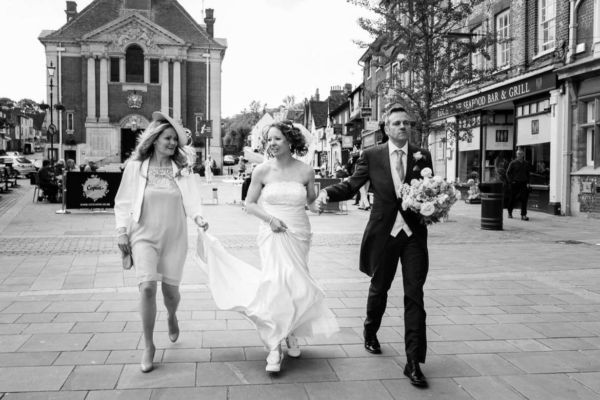 Bride and groom walking through Henley town centre toward the Thames