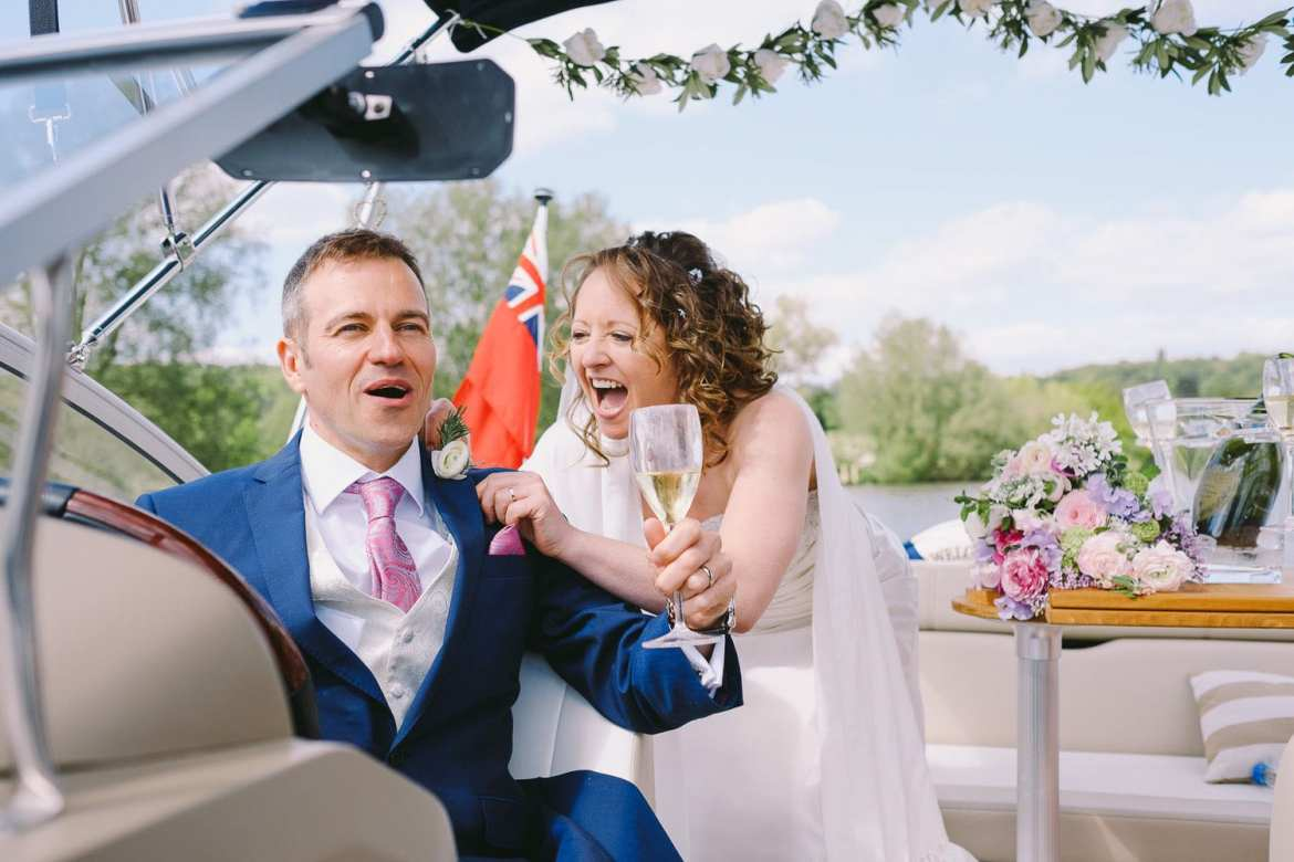 Bride and groom enjoying champagne on the boat trip back to Greenlands