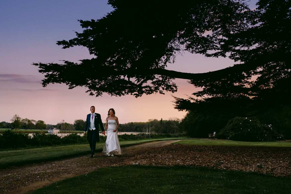 Bride and groom walking next to the Thames at sunset, Greenlands