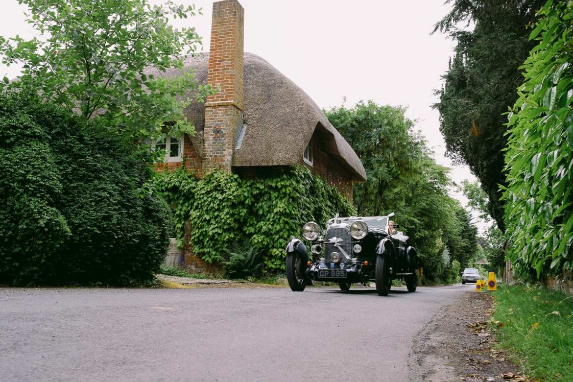 The vintage wedding car approaches the church