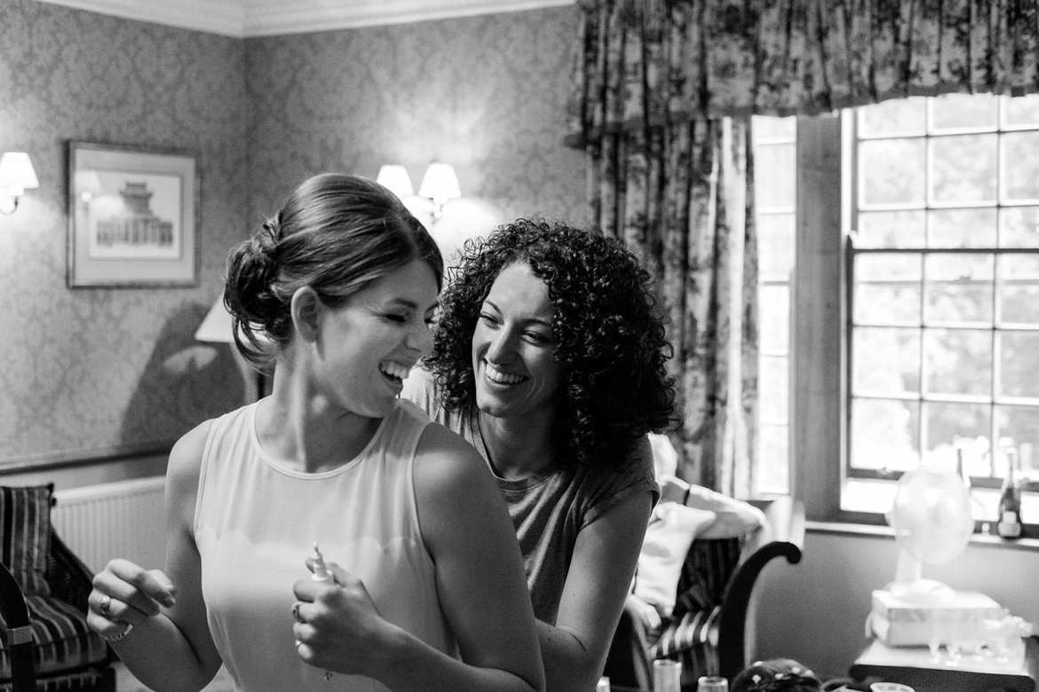 The bride laughing with a bridesmaid