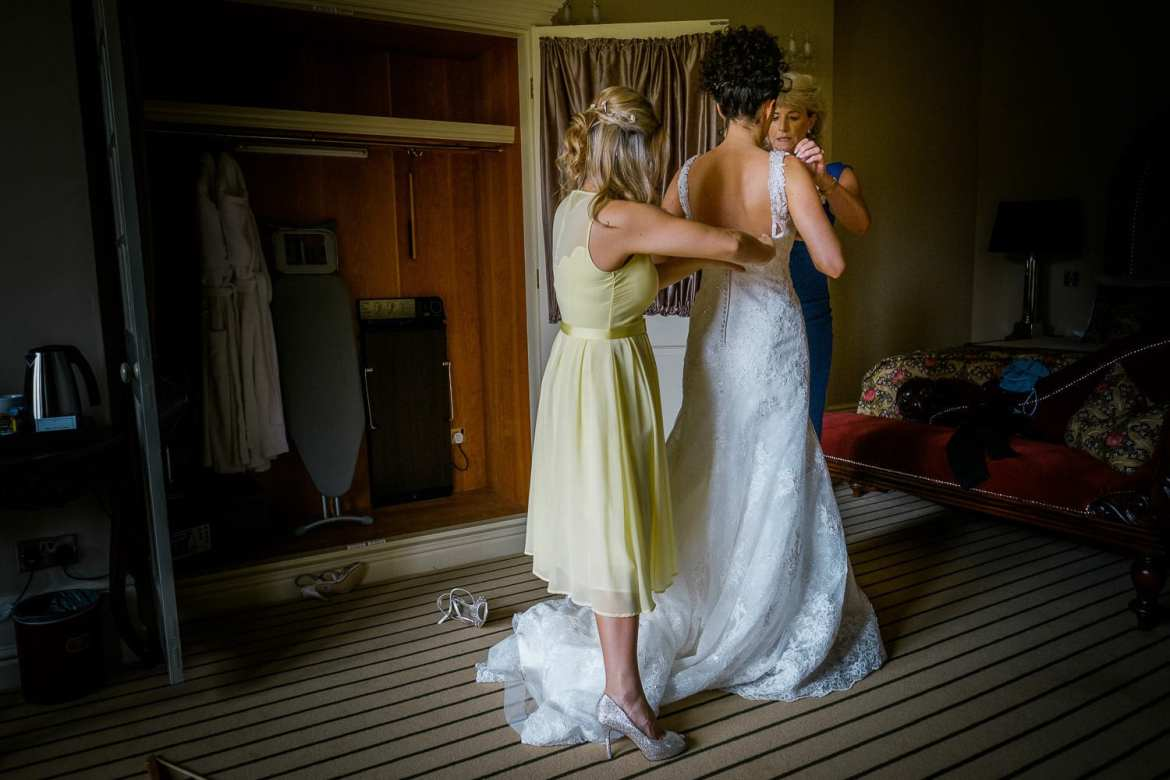 The maid of honour and mum help the bride into her wedding dress