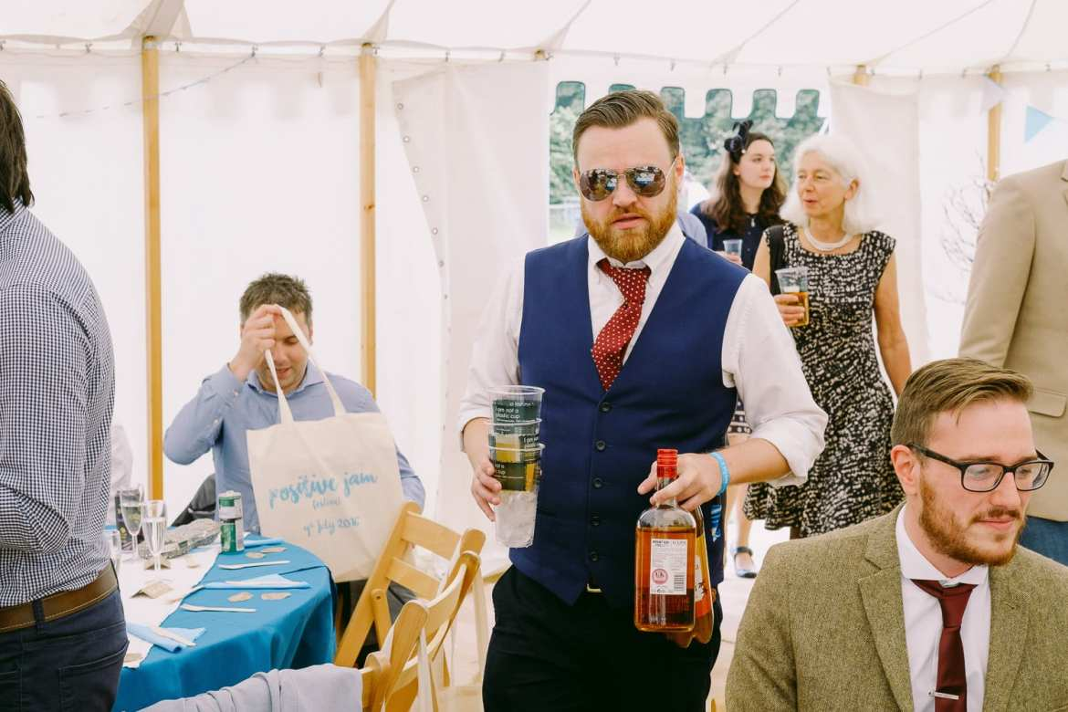 A wedding guest carries two bottles of whiskey