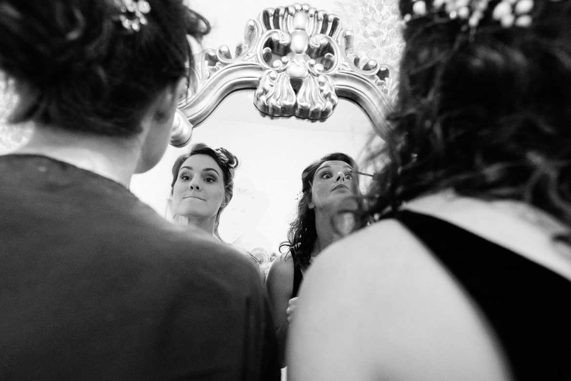 bride and bridesmaid doing their makeup in the mirror