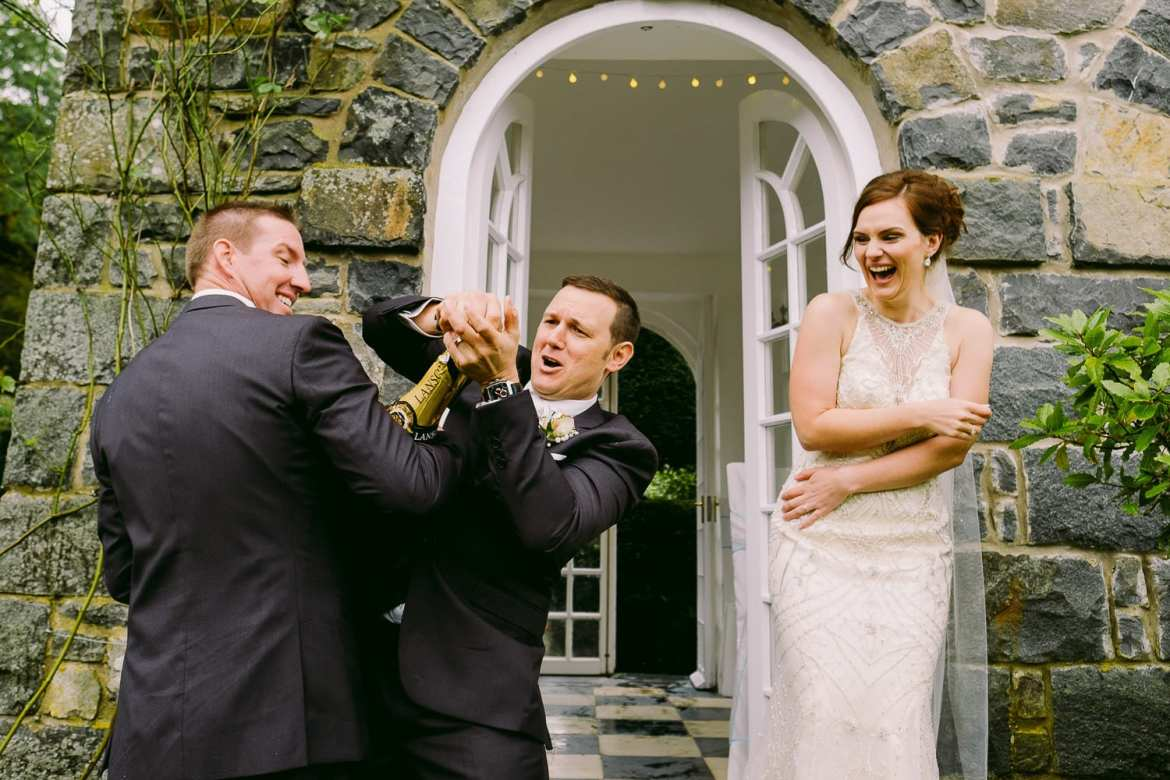 The bride laughs watching the groom and best man trying to open the champagne
