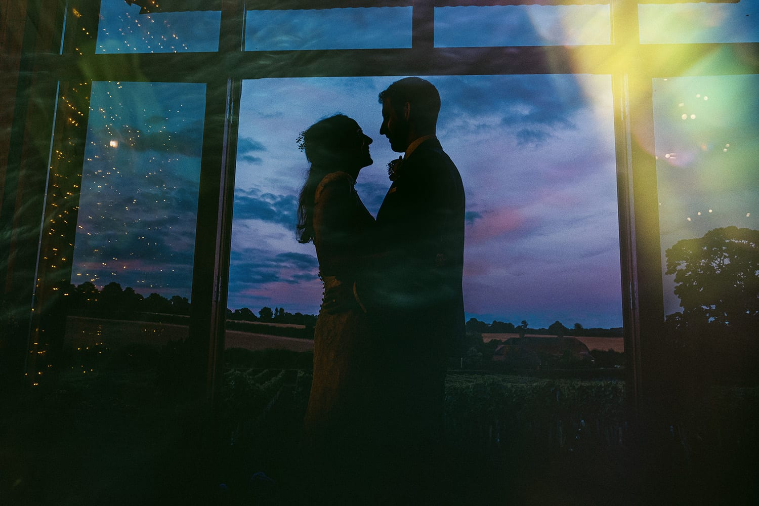 Bride and Groom silhouetted in the doorway at Orpenham Farm Barn