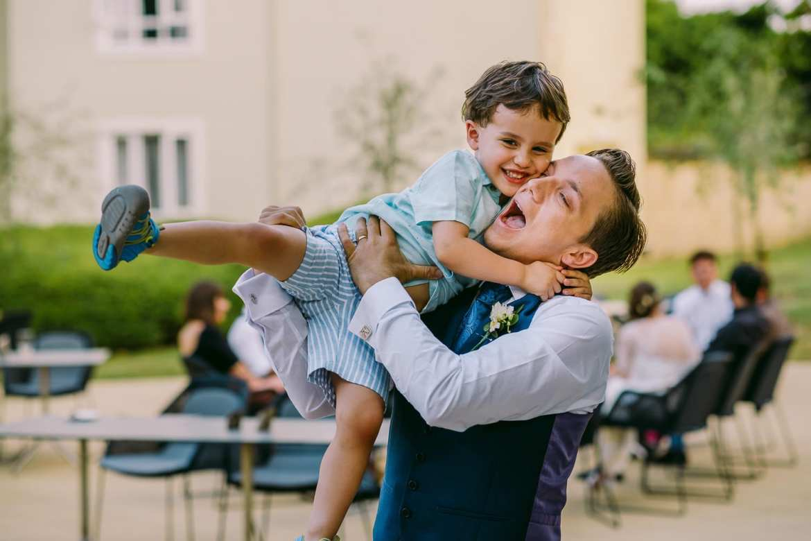 The groom lifts up one of the little guests
