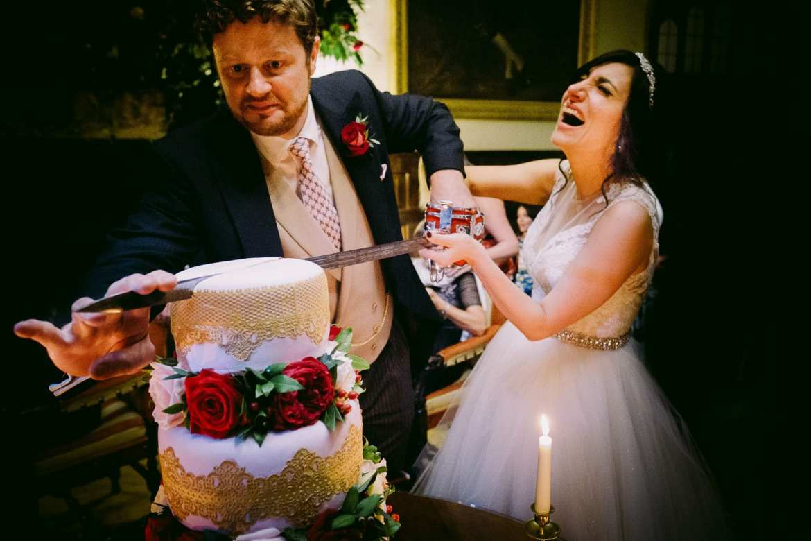 The bride laughs as the couple cur the cake