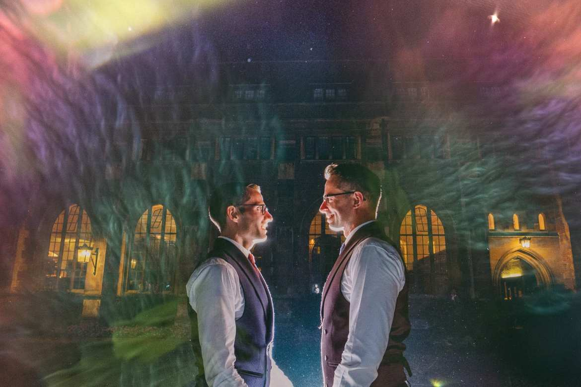 The grooms portrait at night in the garden during a same sex wedding at Pembroke college Cambridge