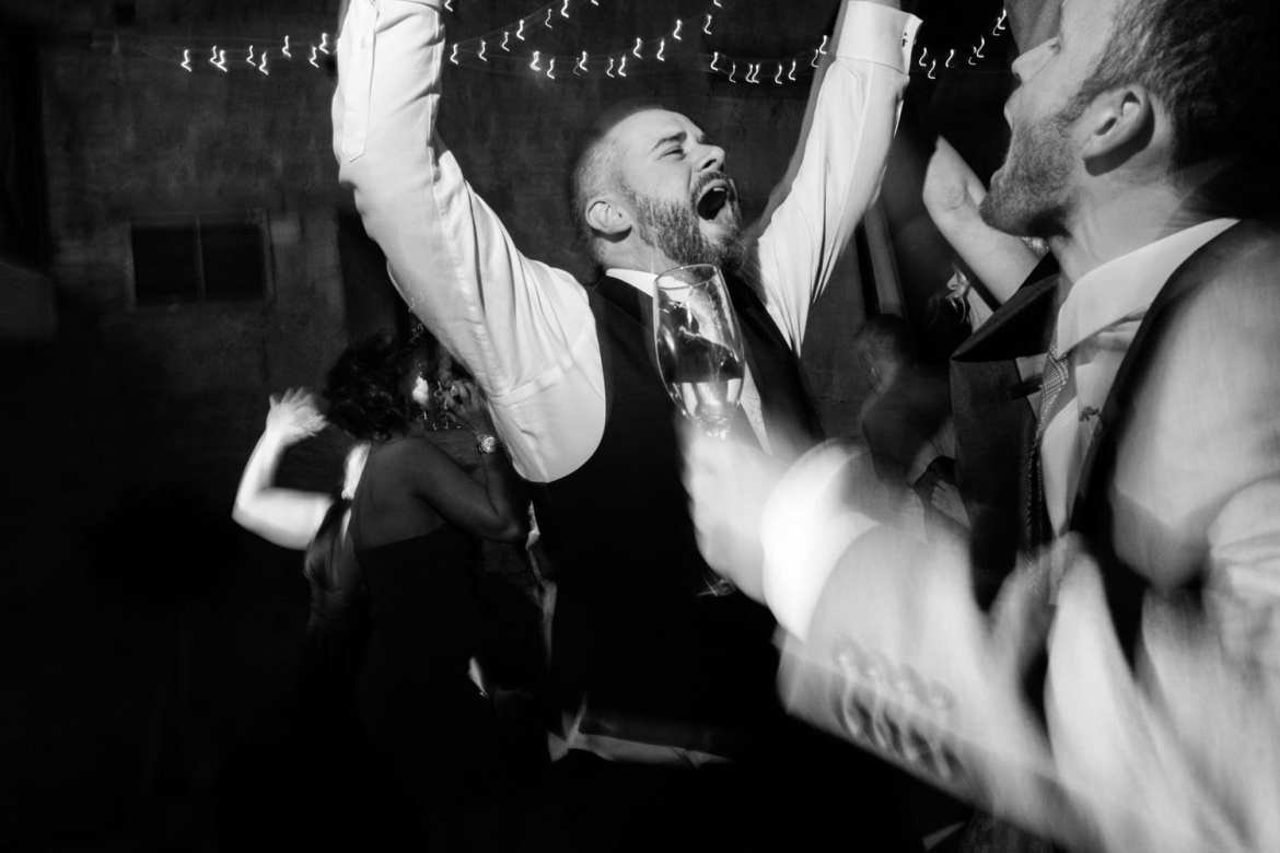 The bride and groom celebrate with their arms in the air