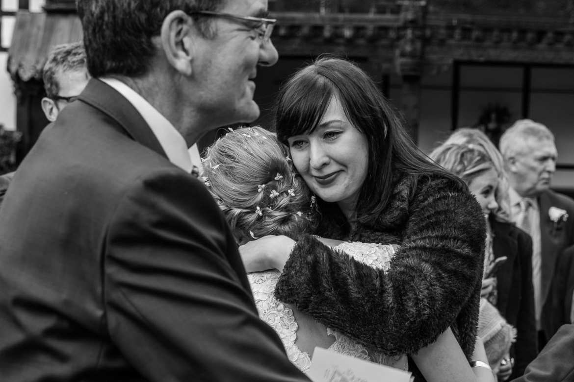 Black and white image of guest hugging bride