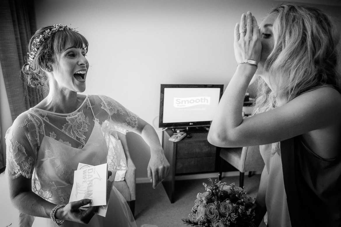 The bride laughs as her bridesmaid pretends to tell her a secret