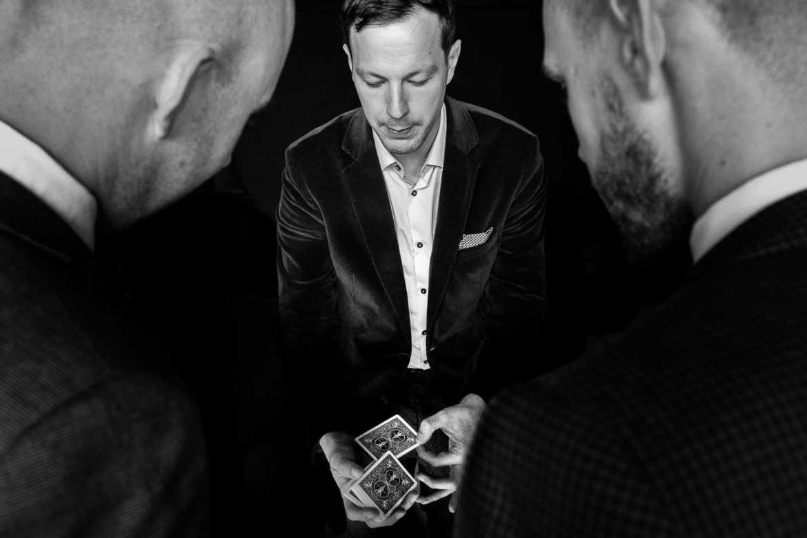A magician does a card trick while two guests look on