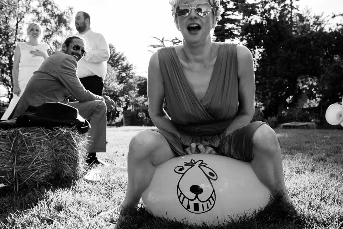 A bridesmaid wearing heart shaped sunglasses bounces on a spacehopper