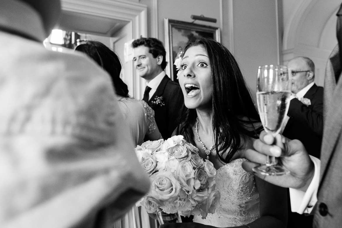 The bride looks surprised and happy to see a friend