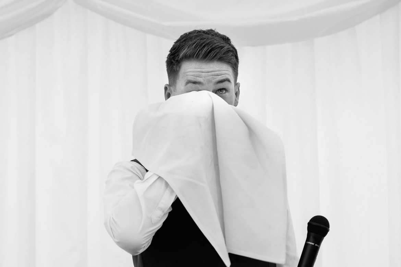 The groom wipes tears away with a huge napkin