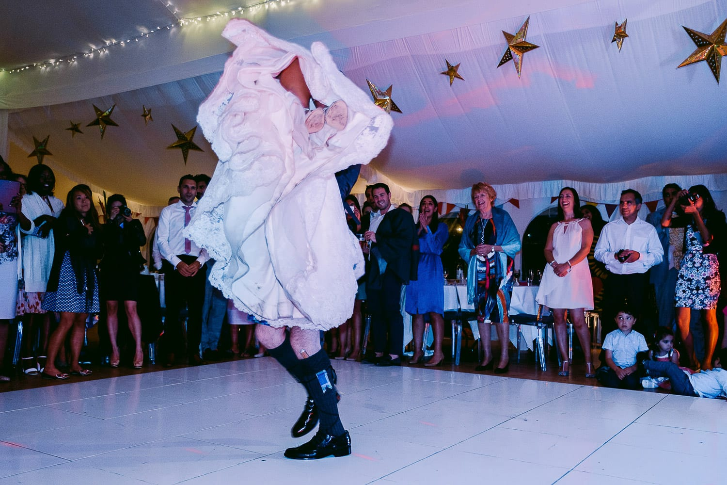 The bride and groom merge into one when he lifts her up on the dance floor