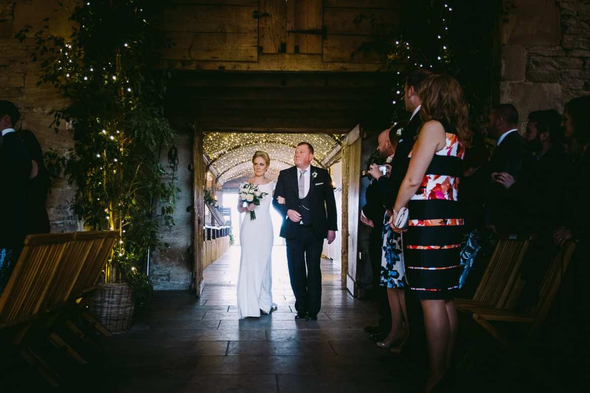 The bride and her father enter the barn