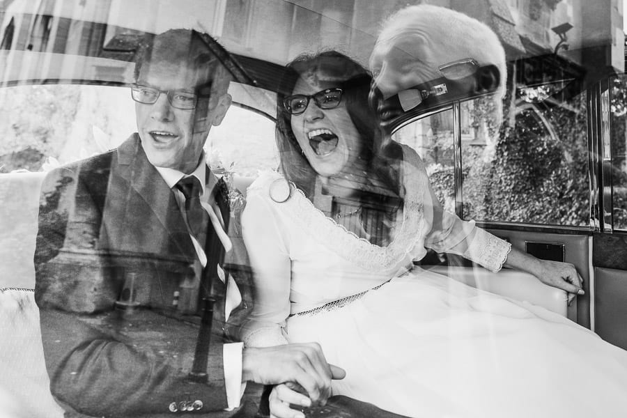 A wedding guest reflected in the car window pulls a face at the bride and groom