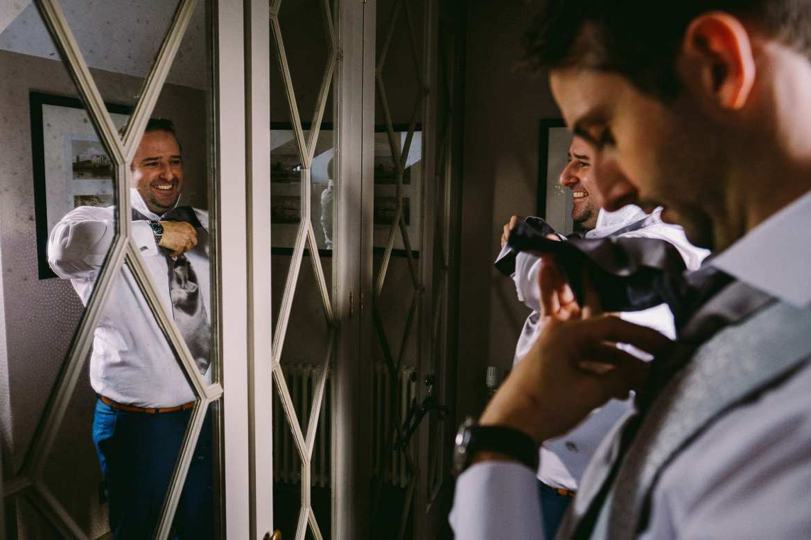 Groom doing his tie in the mirror