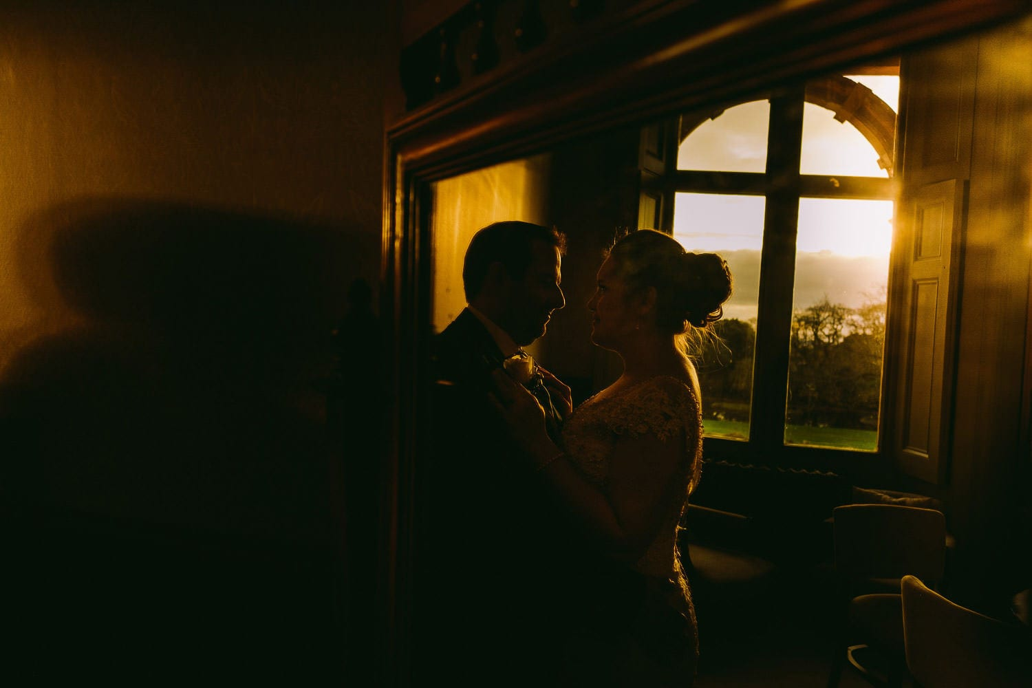 Silhouette of bride and groom by the window