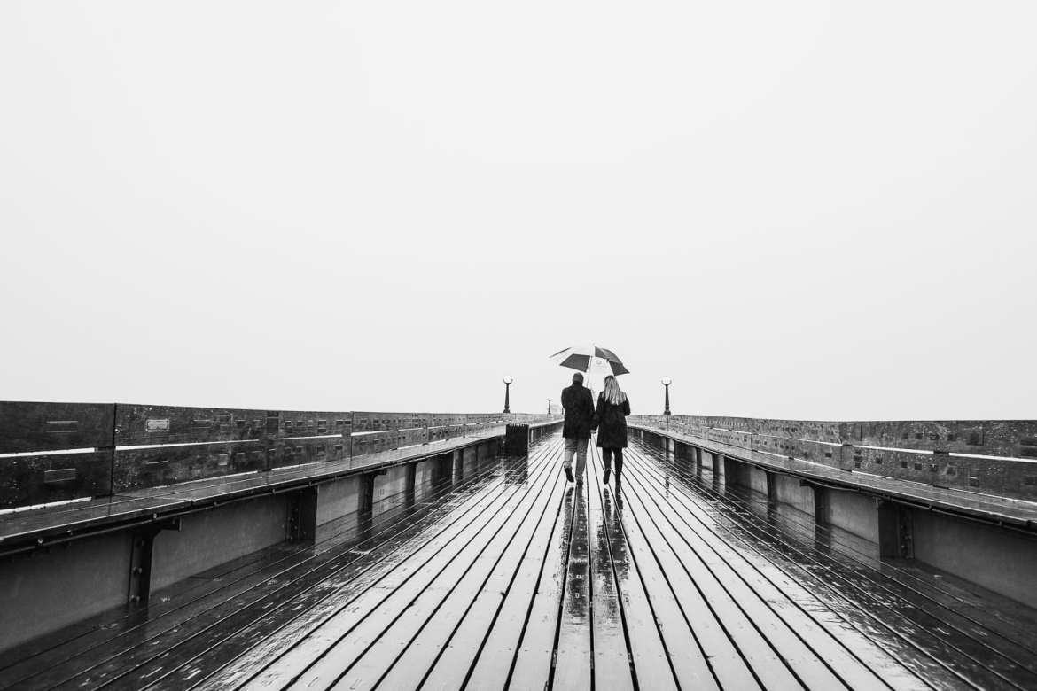 A couple walk along clevedon pier in the rain