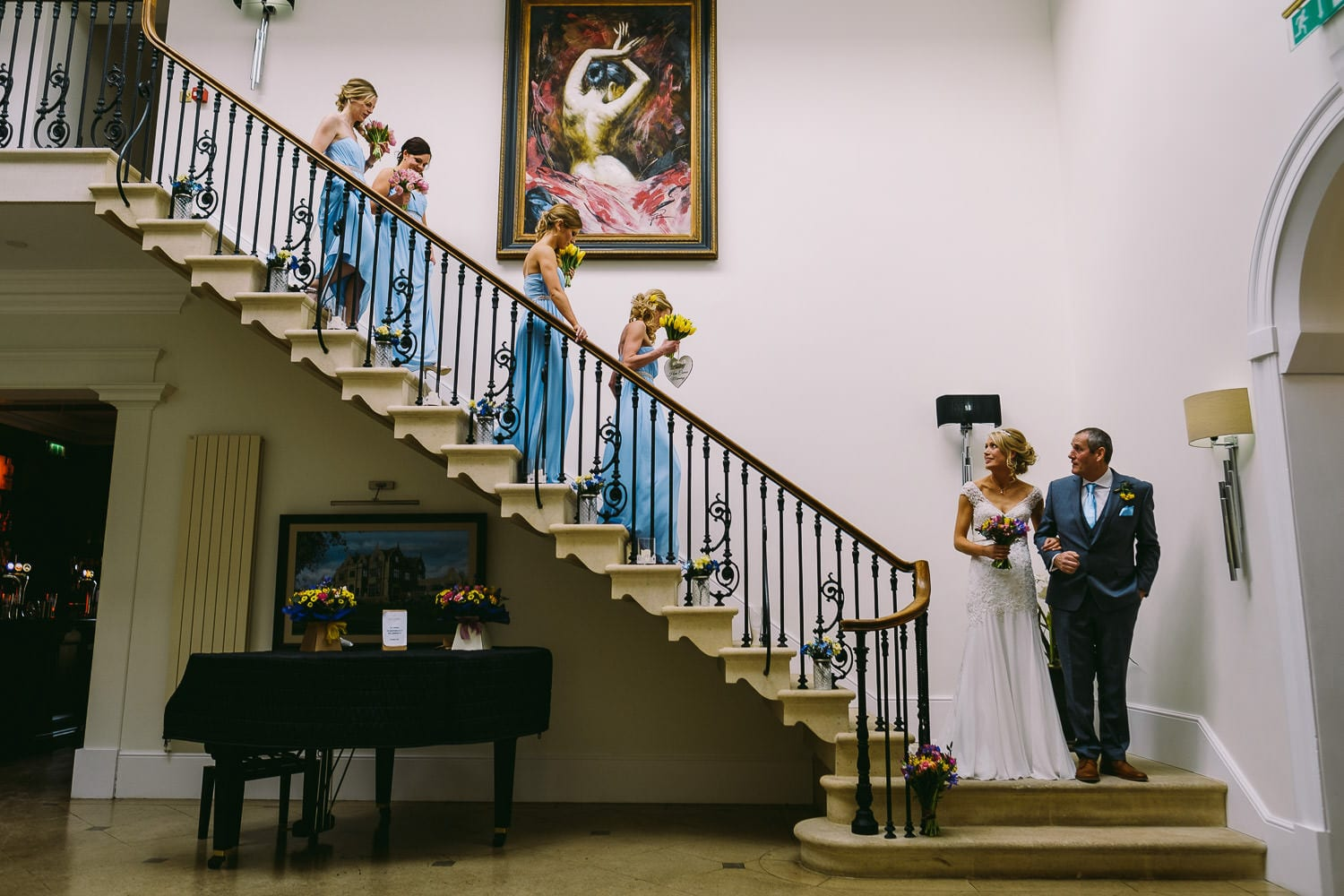 Bride and bridesmaids come down the stairs