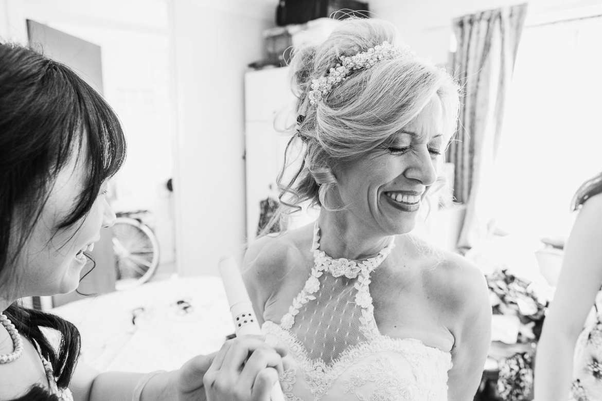 The bride is laughing as her bridesmaids do her hair