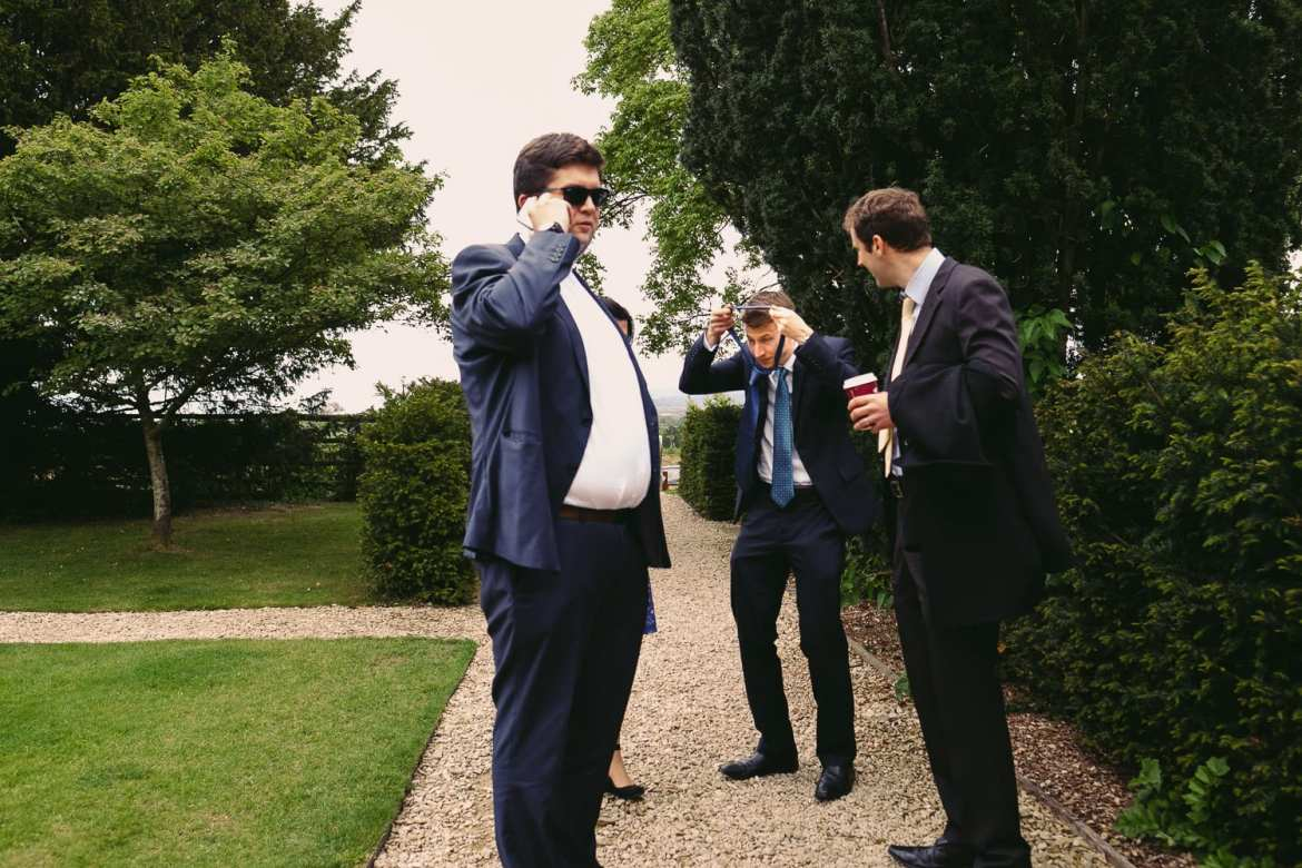 Guests tie their ties in the garden at Elmore Court