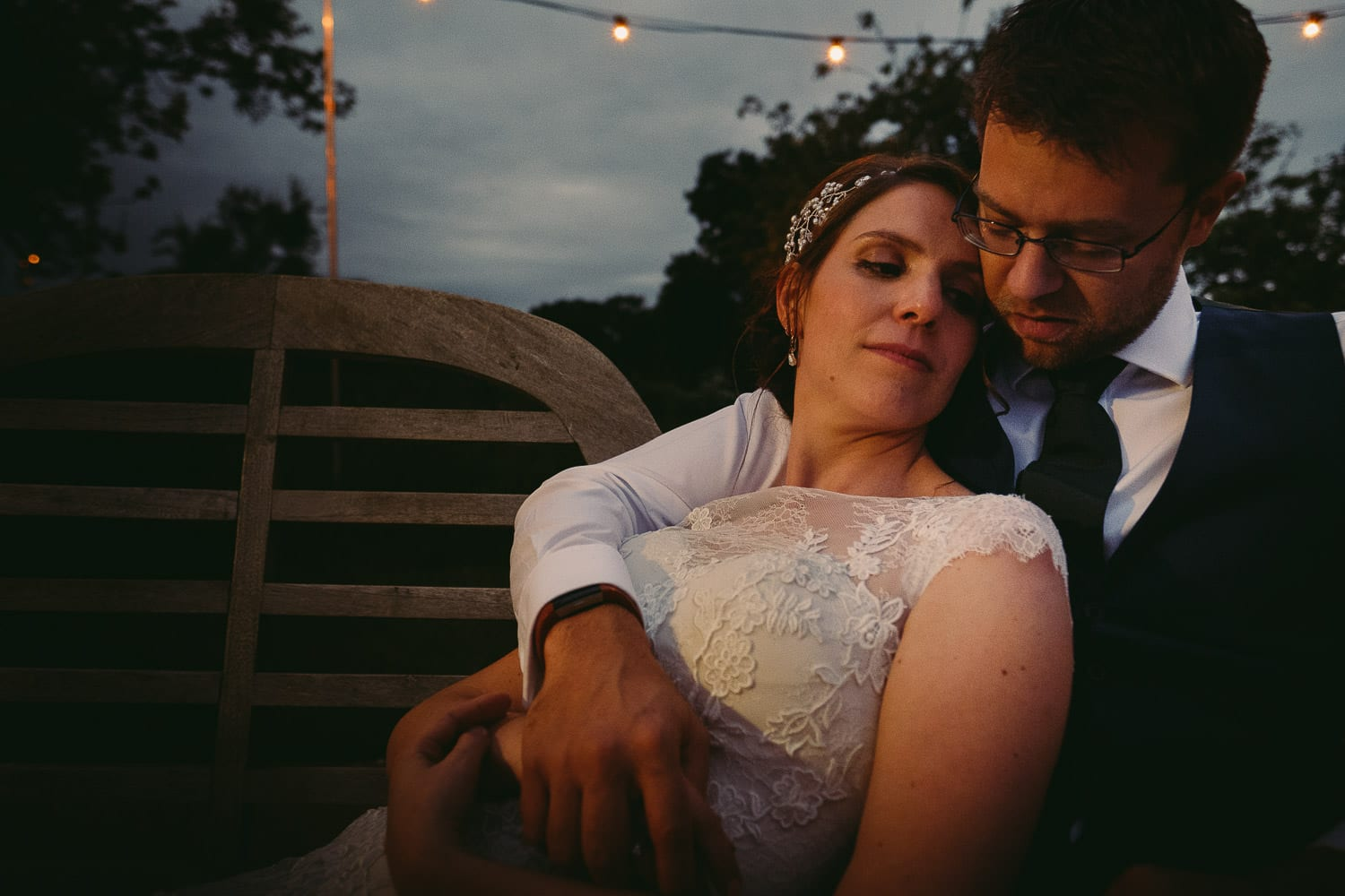 The bride and groom sat on a bench in the evening