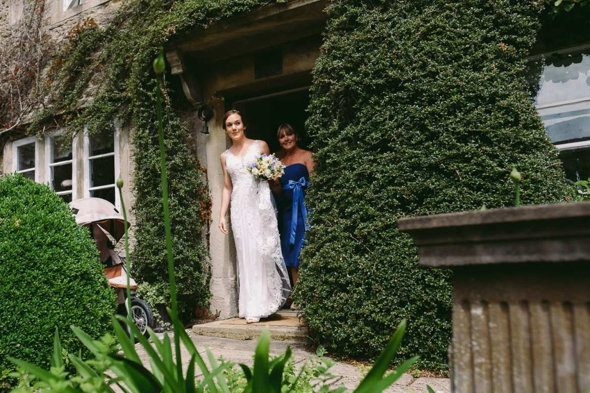 The bride peeks out from the house