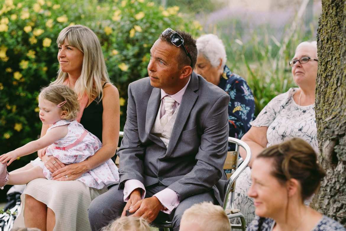 Guests sit in the garden watching the wedding ceremony