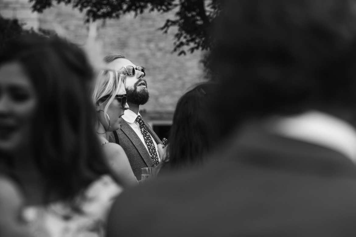 Wedding guest in sunglasses looking at the sky