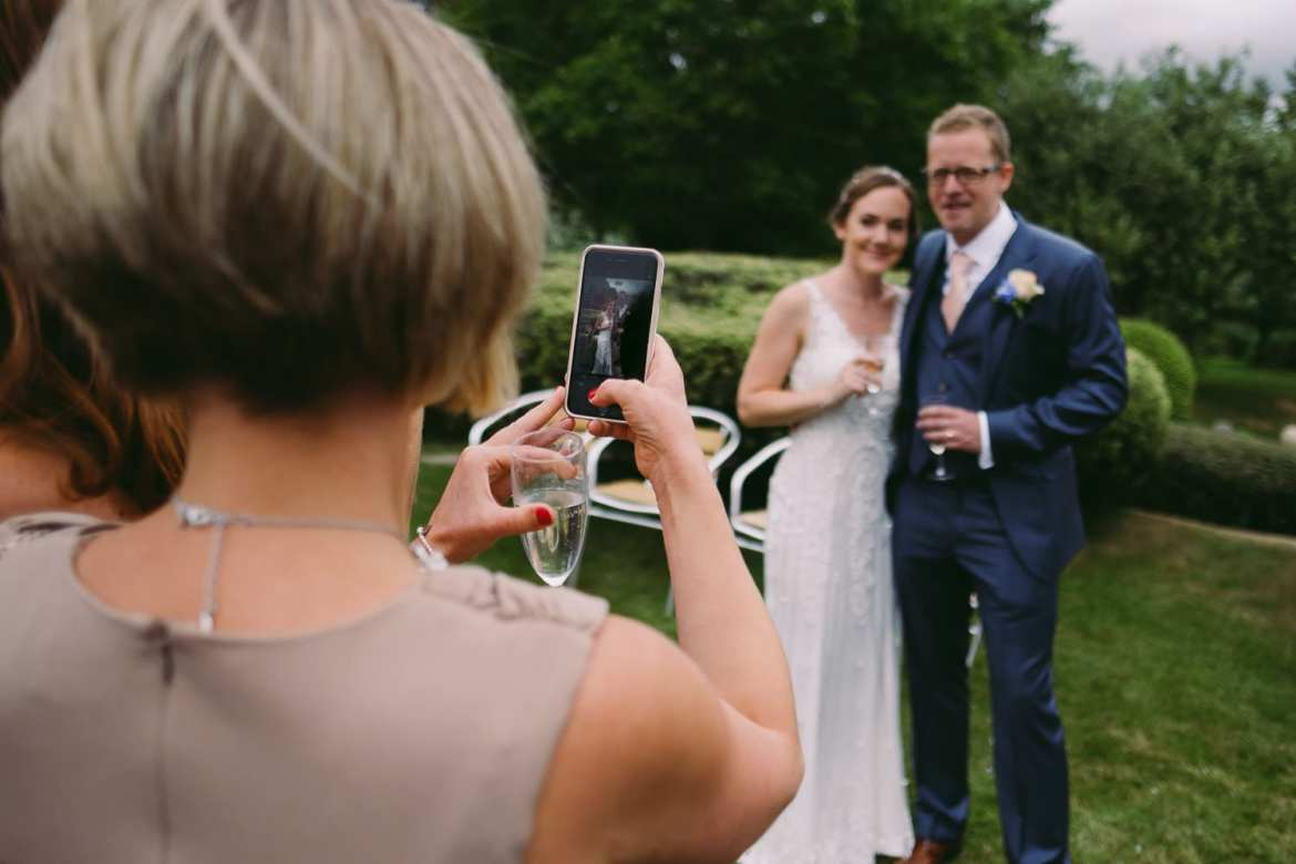 A wedding guest takes a picture of the couple on her iphone