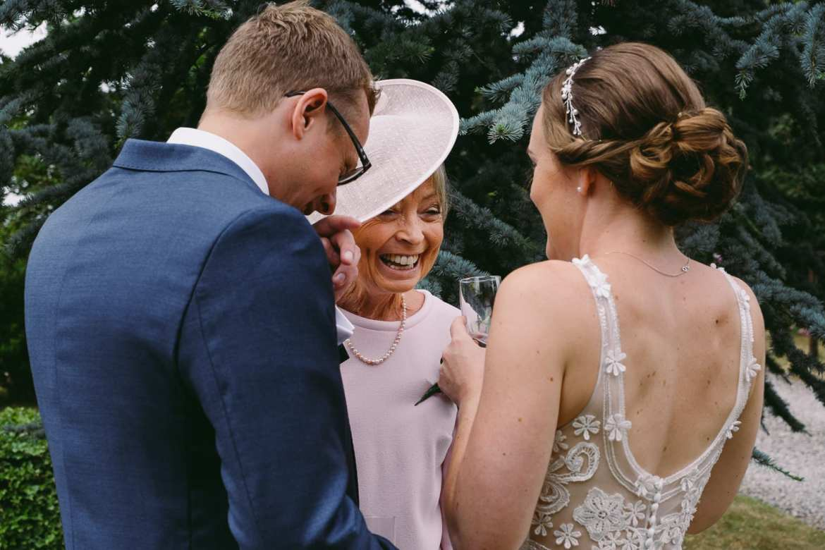 The mother of the bride laughing with the couple