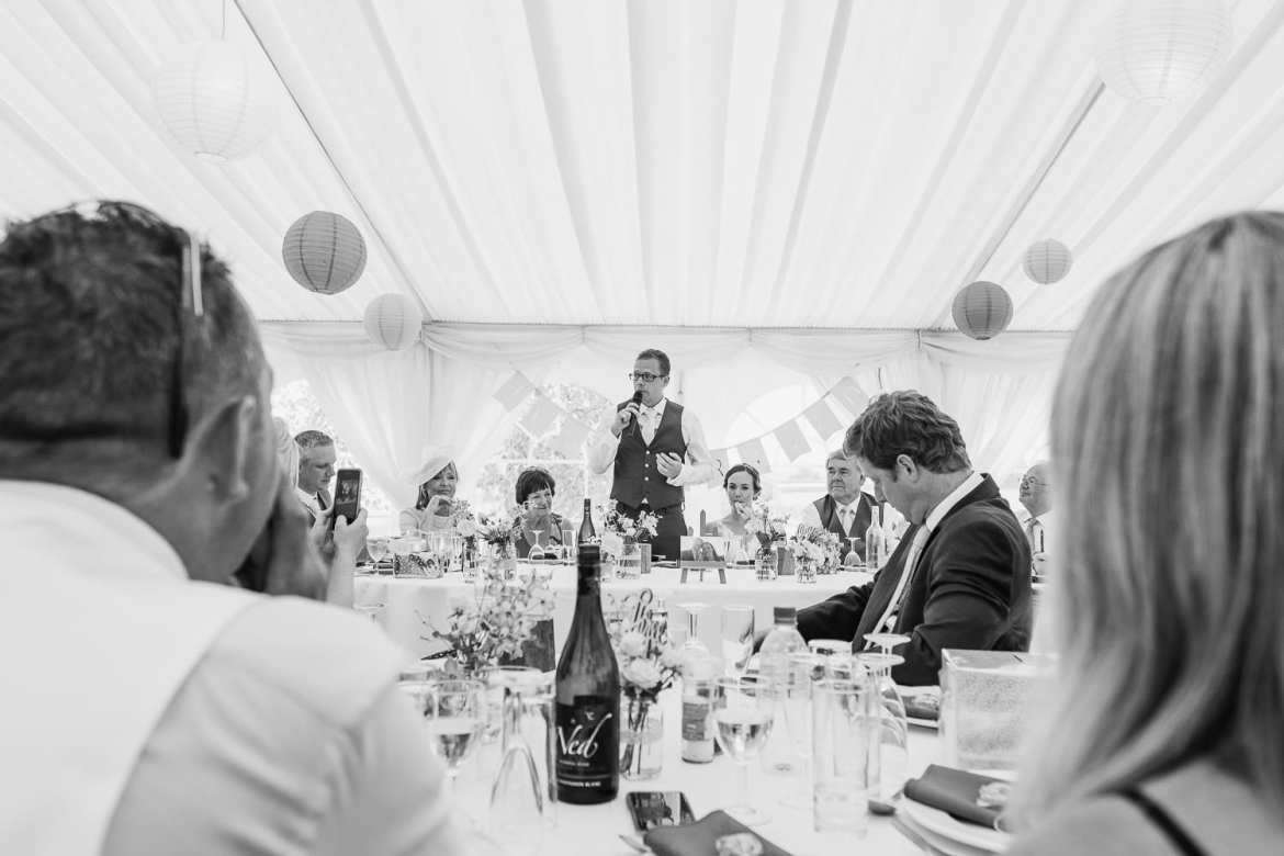 A view through the guests to the groom giving his speech