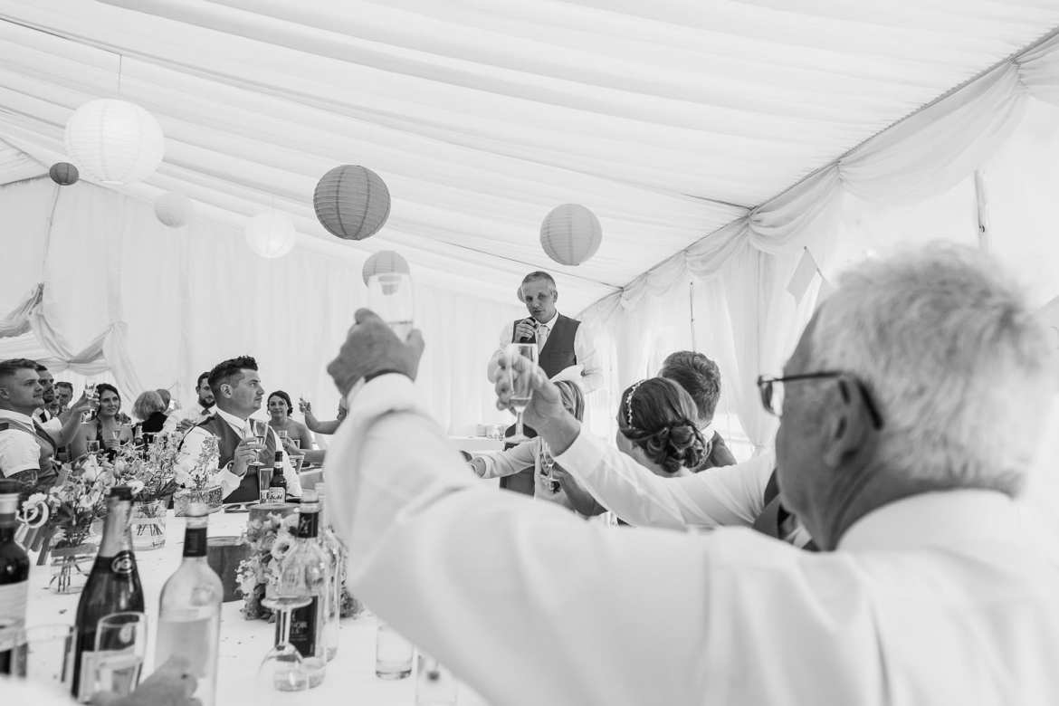 The guests raise their glasses for the best mans speech