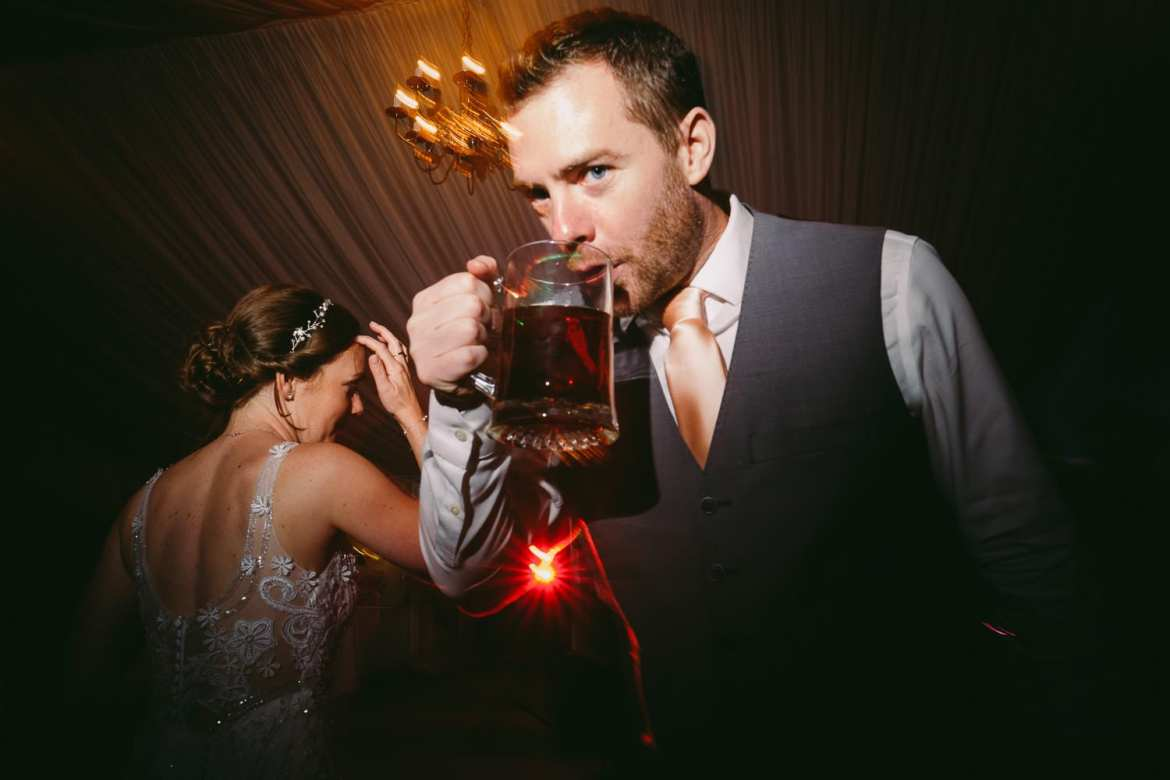 The groom's brother drinking a pint on the dancefloor
