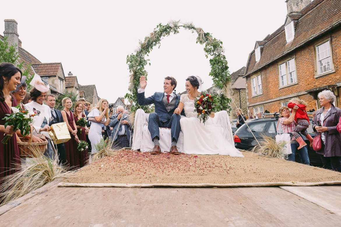 The bride and groom leave the church on a tractor and wave at guests