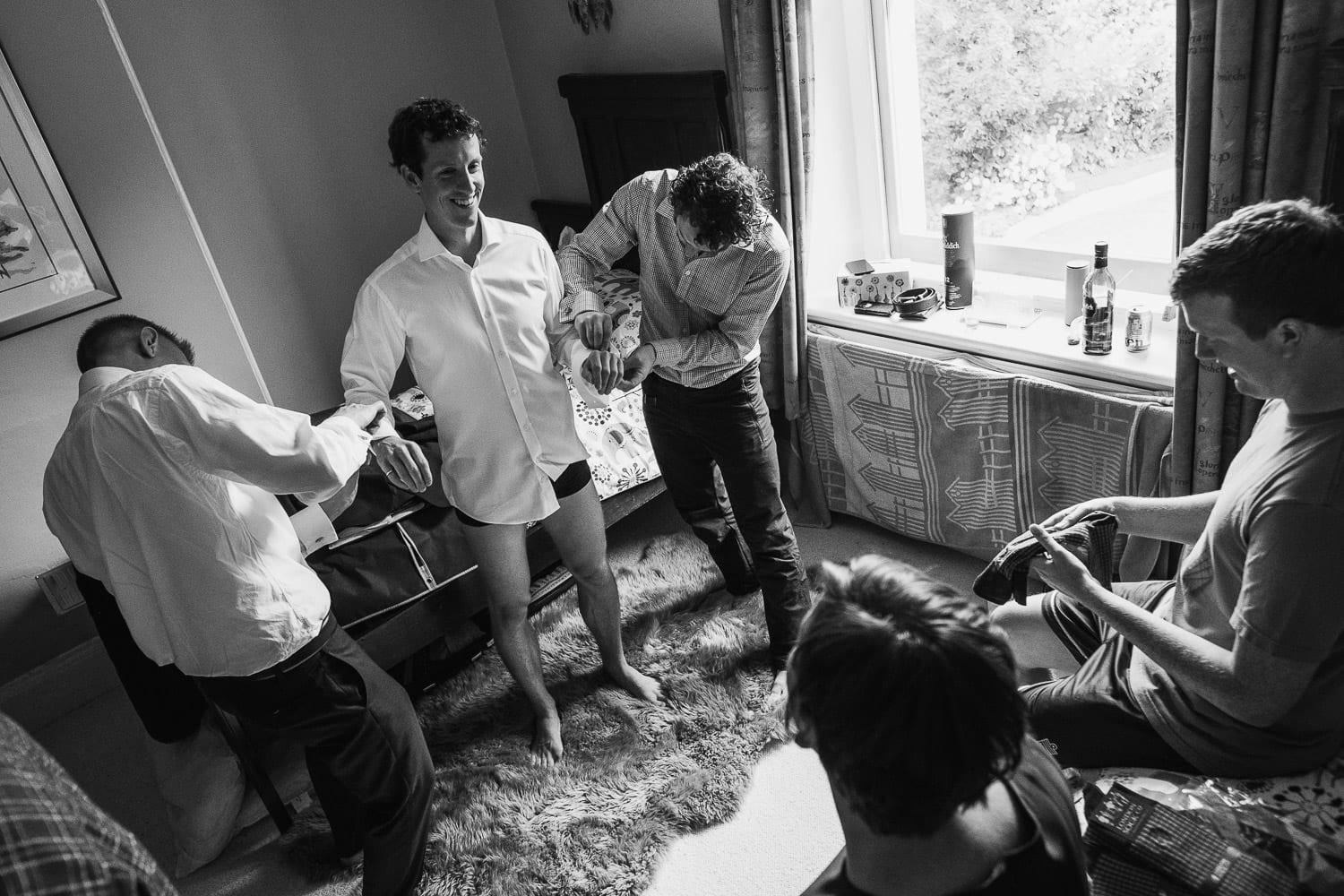 The groomsmen help the groom get dressed