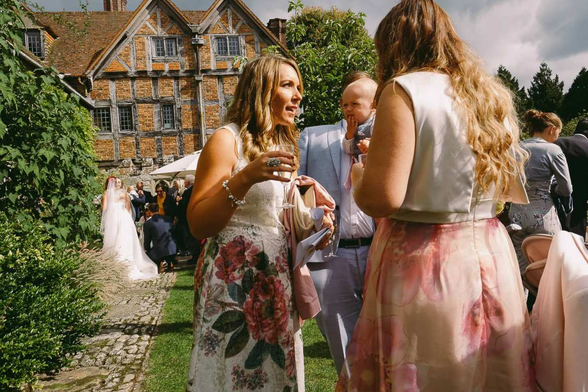 Wedding guests talking in the moated garden