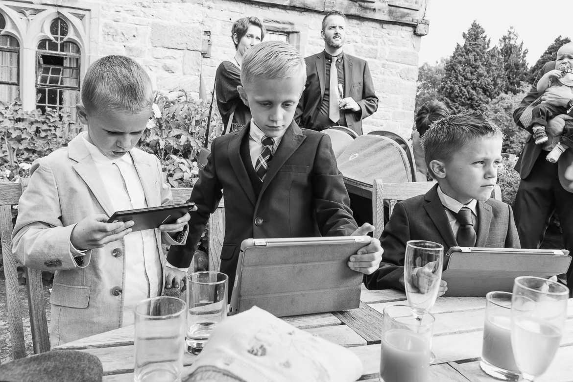 Children in suits look at ipads