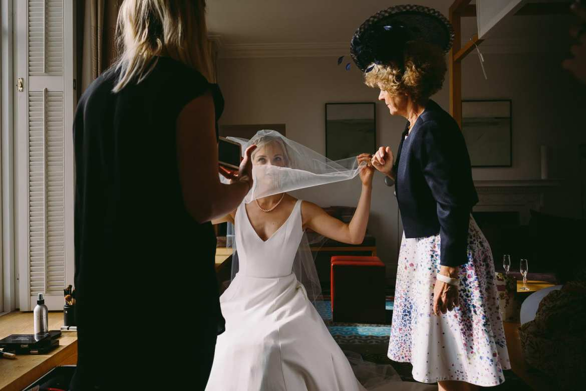 Bride having her veil put on by mum