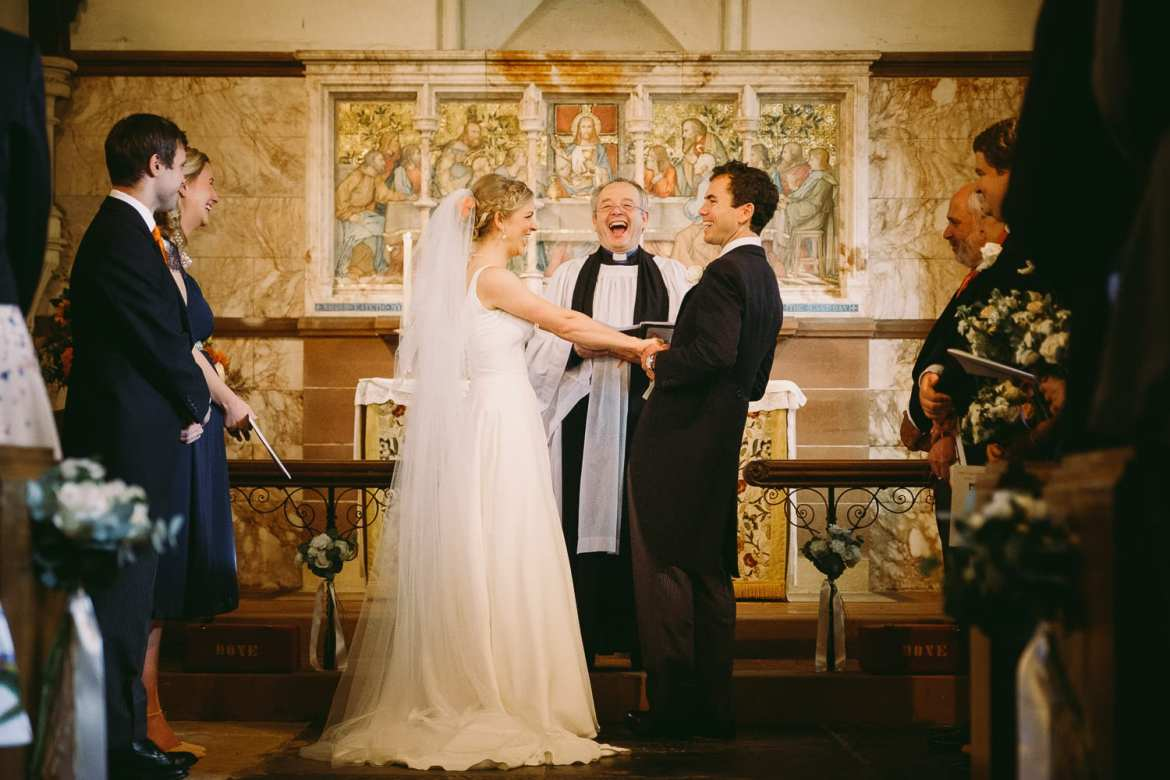 Bride and groom laughing with the vicar in church