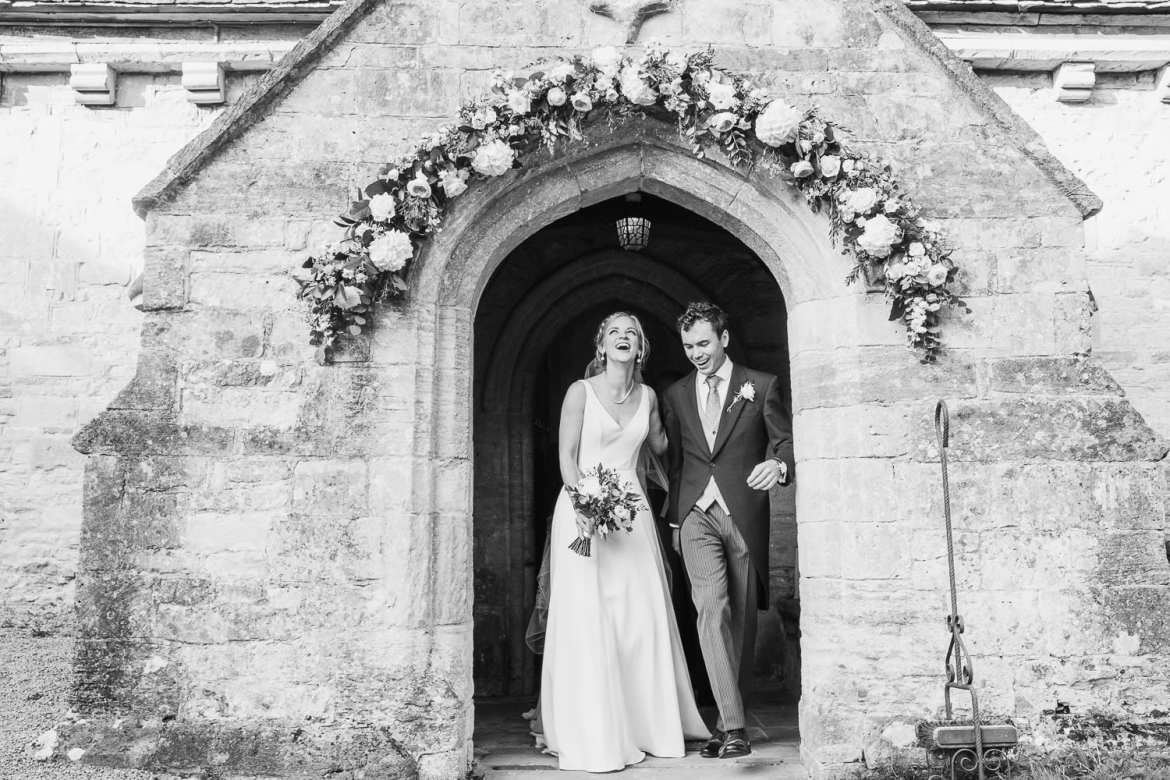 Bride and groom exiting the church at Cowley Manor