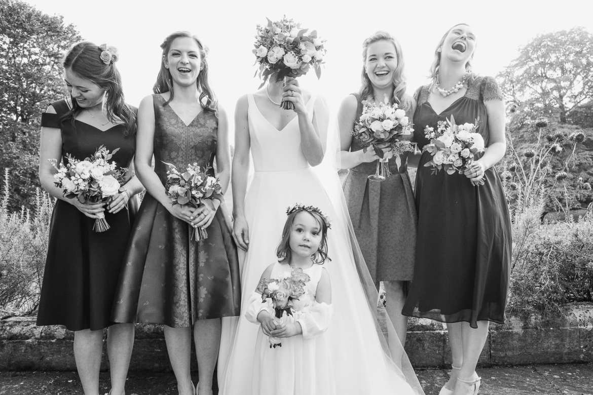 Bride with her bridesmaids and flower girl outside Cowley Manor