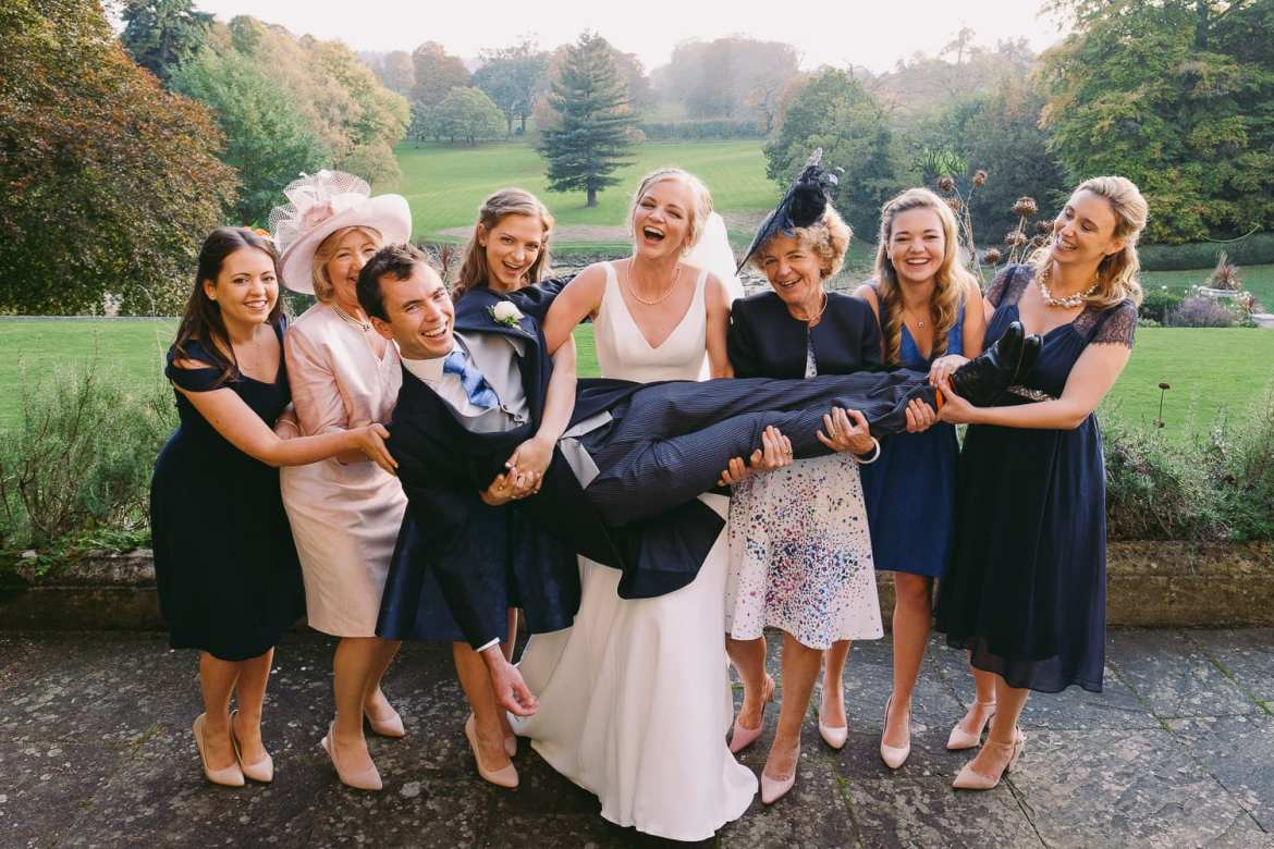 Girls lifting up the groom at Cowley Manor