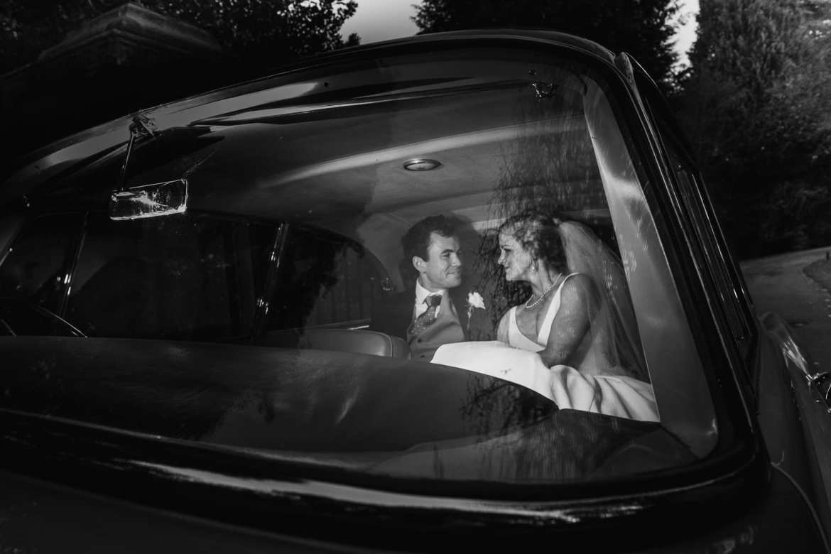 Bride and groom in wedding car outside Cowley Manor